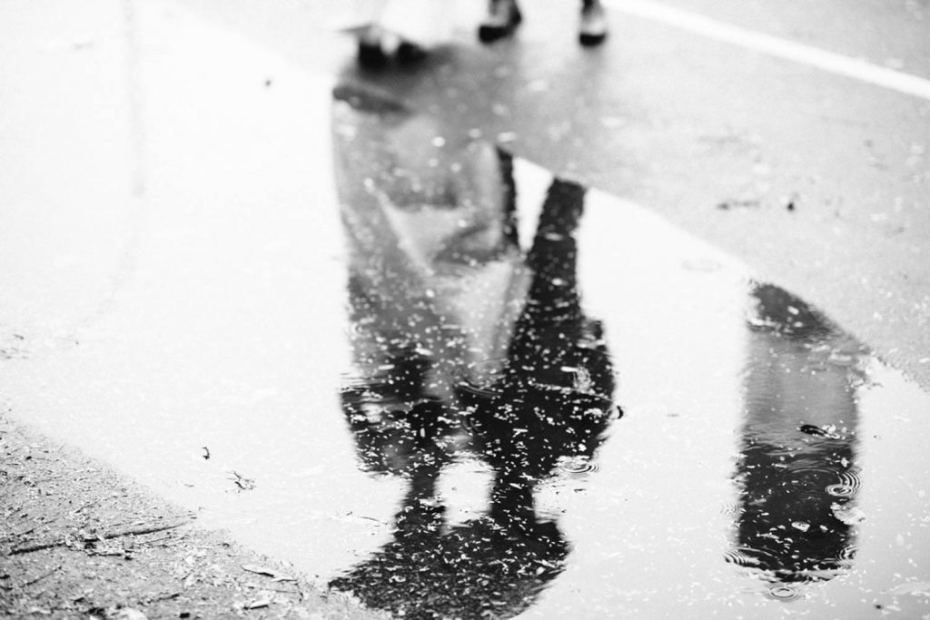 Reflection of bride and groom in a puddle in NYC